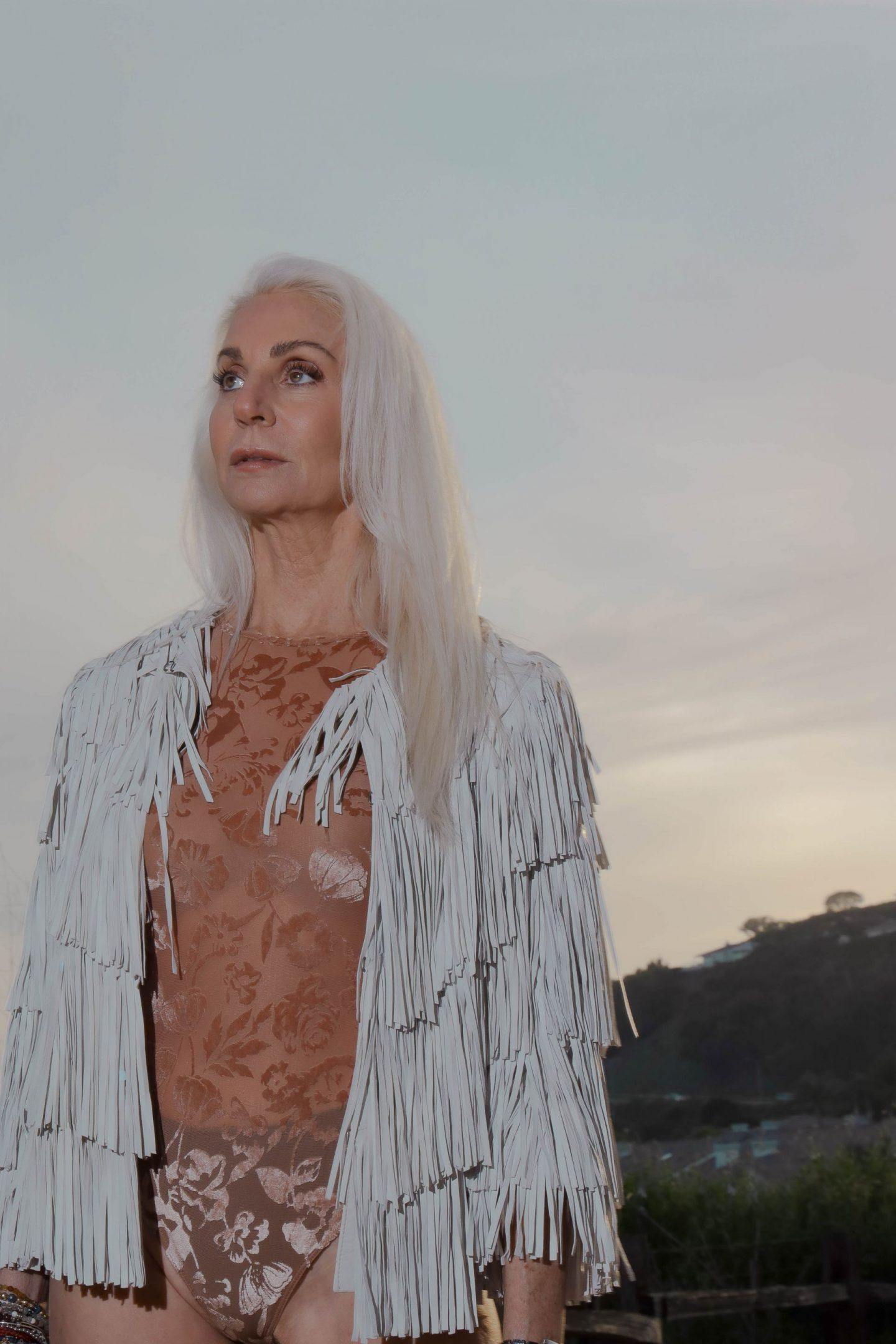 mental health blog post, embracing turning 60, silver haired model, inclusive model, fringe jacket